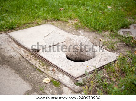 Large stone in drain cover hole, dangerous pavement fragment in Warsaw, Poland, horizontal orientation, nobody. - stock photo