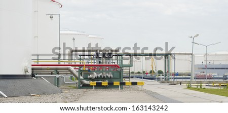 large storage tanks for oil and petrol in the amsterdam harbor area. The red pipelines are for water supply in case of an fire emergency - stock photo