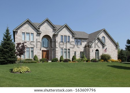 Large suburban home with arched entry - stock photo