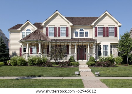 Large suburban home with yellow siding and red shutters - stock photo
