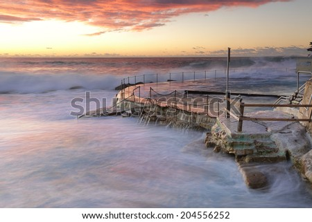 Large swell and surf crashing over the railings, no swimming at Bronte Beach baths today - stock photo