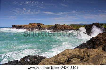 Large swell smashing waves over metres high rock columns and the headland at Bombo Kiama Australia - stock photo