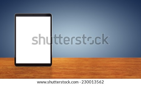 Large tablet with blank screen sitting on wooden counter top with blue background , copy space , Mobile device - stock photo