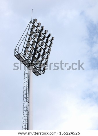 large tall high outdoor stadium spotlights on rigid frame construction with blue sky background - stock photo