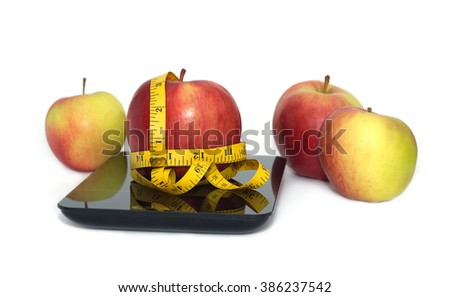 Large  tasty red and yellow ripe apples on kitchen scales and measuring tape isolated on white background. Top view closeup - stock photo