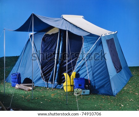 Large tent on grass and blue background camping outdoors - stock photo