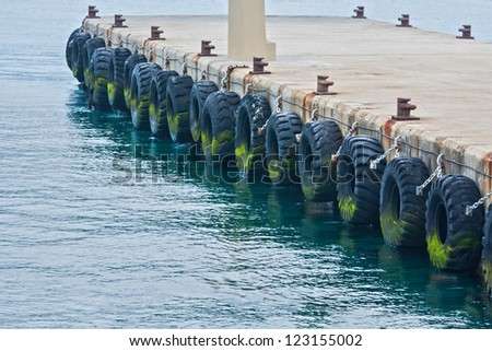 large tires used on pier or warf to protect commercial boats when tied up in harbor - stock photo