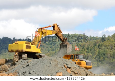 Large tracked excavator loading a articulated dump of rock