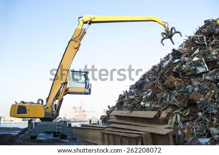Large tracked excavator working a steel pile at a metal recycle yard - stock photo
