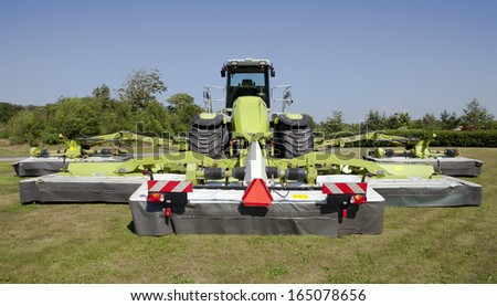 Large tractor with several disc mower attachment. - stock photo