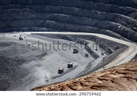 Large trucks being filled with ore at the bottom of an open cast mine. Barrick Cowal Gold Mine in New South Wales, Australia. - stock photo