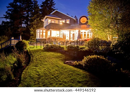 Large two story house with lots of lights in the summer evening. View of backyard garden with lawn. - stock photo