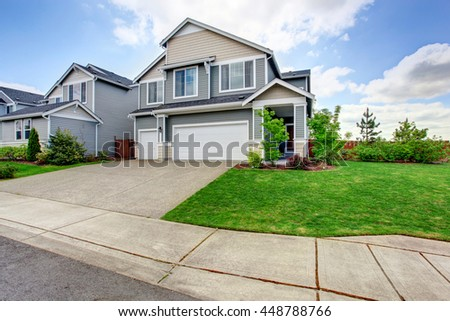 Large two story house with siding, two garage spaces and concrete driveway. View of grass filled garden - stock photo