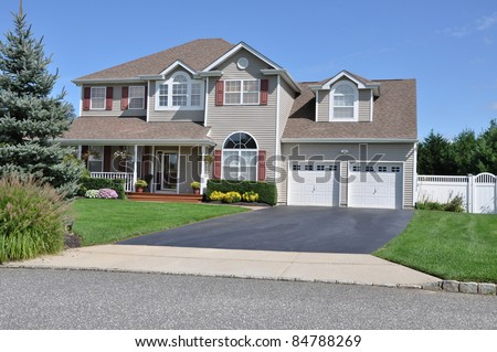 Large Two Story Two Car Garage Suburban Home Driveway Landscaped Front Yard - stock photo