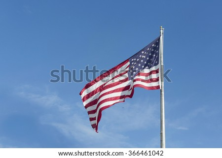 """Large U.S. Flag """"Old Glory"""" blowing in a strong wind on a blue sky - stock photo"""