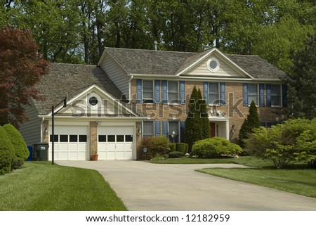Large upscale suburban house surrounded by trees