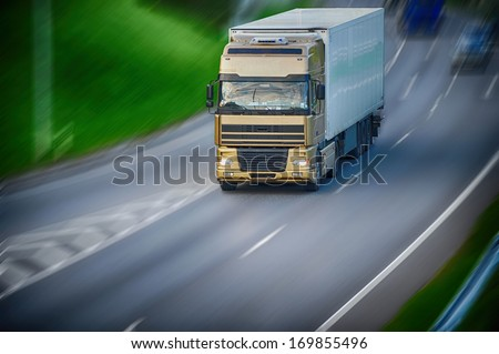 large van with  load moves along  road - stock photo