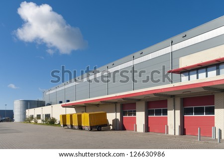 large warehouse with red loading docks and several trailers for rent - stock photo