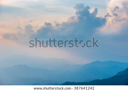 Large warm tone cloud over step jungle on mountain.