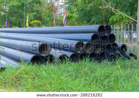 Large water pipes on the grass - stock photo