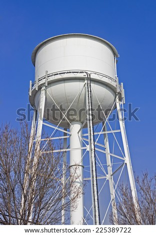 Large water tower stands high in a rural community. - stock photo