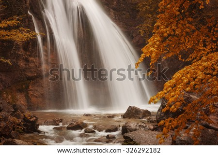 Large waterfall in autumn forest - stock photo