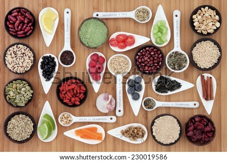 Large weight loss and diet super food selection in bowls and measuring spoons over bamboo background. - stock photo
