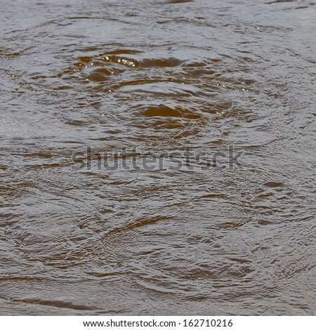 large whirlpool in the center of a river - stock photo