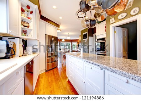 Large white and green kitchen with hardwood floor. - stock photo