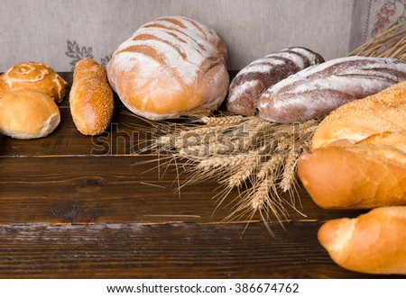 Large whole loaves of freshly baked artisan bread with wheat stalks on dark wooden table with empty area for other objects - stock photo