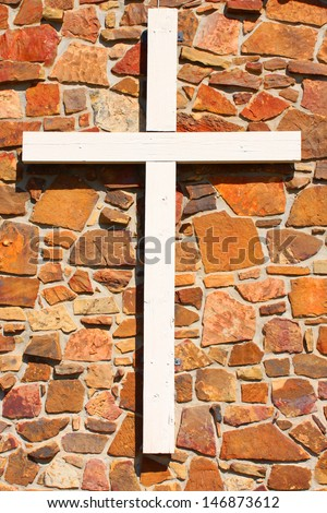 Large wooden cross on a stone wall - stock photo
