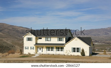 large yellow country house on a hill with scenic view - stock photo