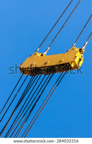 Large yellow pulley assembly with three sets of pulleys and tightly stretched diagonal steel cables above and below. - stock photo