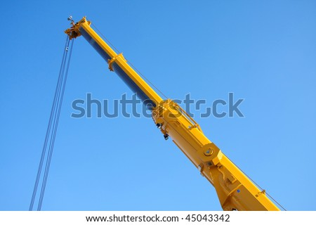 Large yellow telescopic crane, isolated on blue sky