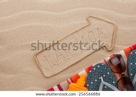 Larnaca  pointer and beach accessories lying on the sand, as background - stock photo