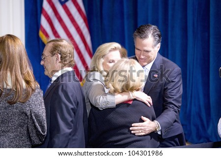 LAS VEGAS - FEB 2: Mitt and Ann Romney hug an unidentified person at the Trump hotel on February 2, 2012 in Las Vegas, Nevada. Donald Trump has endorsed Romney for president. - stock photo