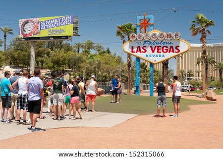 LAS VEGAS - MAY 23: People posing by the iconic 'Welcome to Las Vegas' sign on May 23, 2013 in Las Vegas. It was designed by Betty Willis in 1959 and cost $4,000 to build and install.  - stock photo