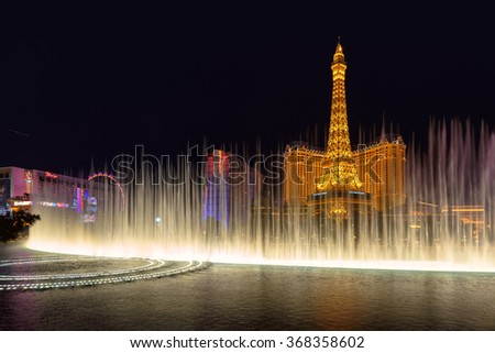 LAS VEGAS, NEVADA - MARCH 26: Fountain show at Bellagio hotel and Eiffel Tower at background  in Las Vegas, Nevada at night on March 26, 2015.