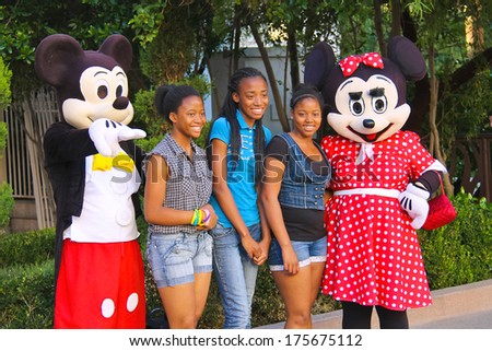 LAS VEGAS, NEVADA, USA - OCTOBER 20, 2013  : Actors in costumes Mickey Mouse  and Mrs. Mickey Mouse posing with tourists for  camera in Las Vegas. Many actors in different costumes entertain tourists