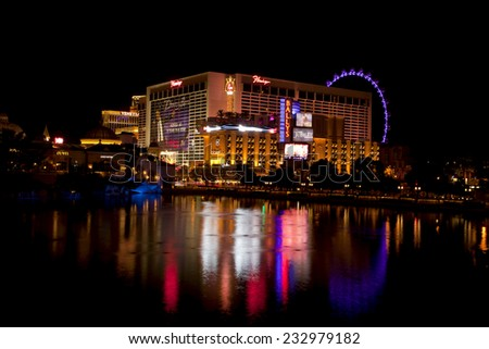 Las Vegas, Nevada, USA - Sept. 25, 2014: The Flamingo Casinos and Hotel with High Roller Ferris Wheel reflecting in the Bellagio fountain lake at night in Las Vegas, Nevada, USA on Sept. 25, 2014: