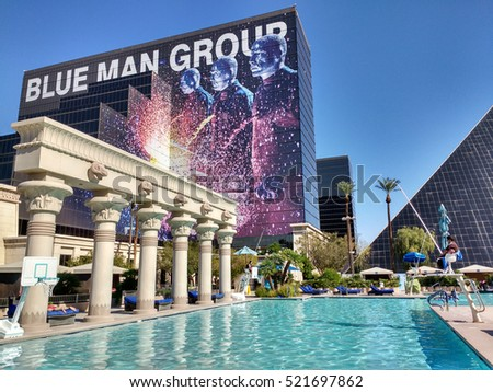 LAS VEGAS, NOV 4TH, 2016: A row of antique columns stands next to the turquoise pool of the Las Vegas' Luxor hotel, with its facade, featuring an ad for Blue Man Group, in the background.