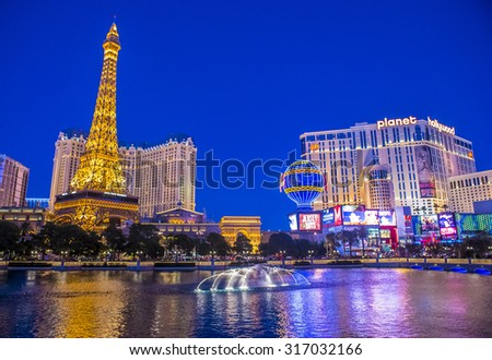 LAS VEGAS - SEP 03 : Night view of the dancing fountains of Bellagio and the Eiffel Tower replica of Paris hotel and Planet Hollywood hotel in Las Vegas Nevada, on September 03 , 2015 - stock photo