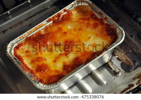 Lasagna in baking tray covered with foil just come out from the oven