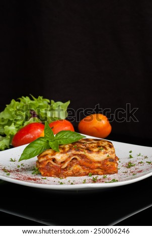 Lasagna on a square white plate with Italian basil