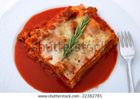 Lasagna on plate with sauce and rosemary herb garnish - stock photo