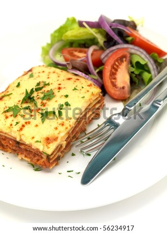Lasagna plated up with a salad and isolated against a white background - stock photo