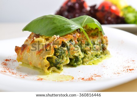 lasagna stuffed with spinach, cheese sauce and a Basil leaf