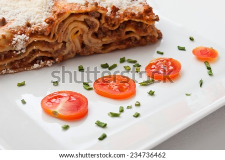 lasagna with cherry tomatoes presentation in a plate