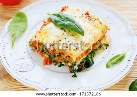 Lasagna with meat and spinach, food closeup - stock photo