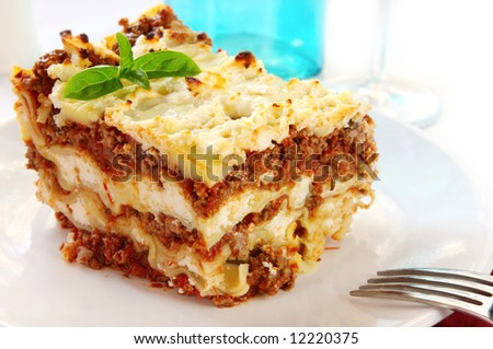 Lasagne, garnished with basil, ready to eat.  Lots of melting mozzarella, ricotta and parmesan cheeses, layered with a meat sauce. - stock photo